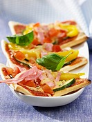 Three pizza slices with ham and vegetable topping