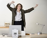 Young businesswoman in office, arms raised, laughing, portrait