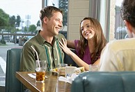 Couple having lunch with friends in diner, smiling
