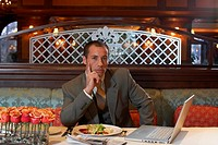 Portrait of business man at restaurant table, newspaper, mobile and laptop by plate