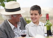 Grandfather sitting with grandson 6-8 outdoors, smiling