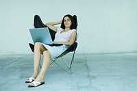 Young woman sitting back in chair, using laptop, full length portrait