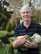 Senior man holding vegetables in garden, smiling, portrait