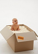 Baby girl 3-6 months lying in box of packing foam