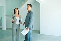 Well dressed man and woman standing in bare home interior, woman holding binder, man holding blueprints