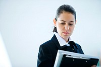 Young businesswoman looking at file, head and shoulders