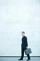 Businessman walking, carrying briefcase, full length