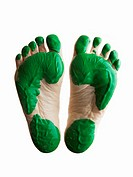 Soles of feet with green paint against white background, close-up