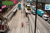 A delivery man taking advantage of the tram way to avoid the congested traffic in Hong Kong, China