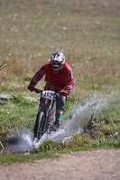 Mountain biker racing through a bog