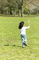 Girl 4-5  playing with Japanese pinwheel in park