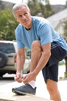 Active senior man, in blue t-shirt and shorts, tying trainer shoelace on driveway wall, side view