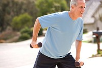 Active senior man, in blue t-shirt, exercising with dumbbell weights on driveway, smiling, side view