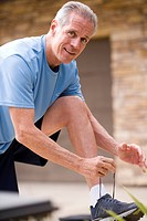 Active senior man, in blue t-shirt and shorts, tying trainer shoelace on driveway wall, smiling, side view, portrait