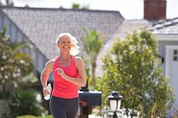 Active senior woman, in pink sports vest, jogging along suburban street, smiling