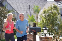 Active senior couple, in sportswear, jogging along suburban street, woman holding plastic water bottle, smiling