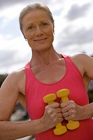 Active senior woman, in pink sports vest, exercising with dumbbells, smiling, close-up, front view, portrait tilt