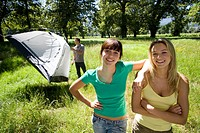 Young man assembling dome tent on camping trip in woodland clearing, focus on two female friends in foreground, smiling, portrait