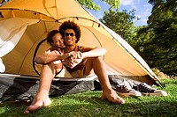 Young couple sitting in dome tent entrance on camping trip, woman embracing man, smiling, front view, portrait surface level