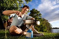 Young man cooking food on gas camping stove near woodland lake, close-up surface level