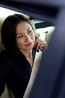 Businesswoman sitting in backseat of car, wearing seatbelt, using mobile phone, view through corner of open window