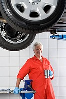 Mature male car mechanic, in red overalls and protective gloves, taking tea break near hydraulic platform in auto repair shop, smiling, portrait