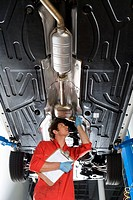 Male car mechanic, in red overalls and protective gloves, looking at underside of car on hydraulic platform in auto repair shop, holding clipboard, lo...