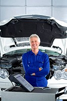 Mature car mechanic, in blue overalls, standing near computer and car with open bonnet in auto repair shop, smiling, front view, portrait