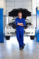 Male car mechanic, in blue overalls, standing in front of car with open bonnet on hydraulic platform in auto repair shop, smiling, front view, portrai...