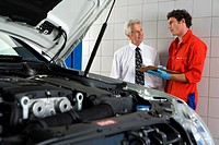 Car mechanic, in red overalls and protective gloves, talking to male customer beside car with open bonnet in auto repair shop, holding clipboard