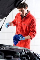 Male car mechanic, in red overalls and protective gloves, looking at car dipstick in auto repair shop, side view