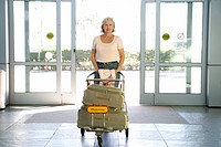 Senior woman entering airport through automatic doors, pushing luggage trolley, smiling, front view, portrait