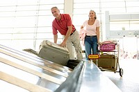 Senior man retrieving suitcase from luggage carousel in airport, senior woman standing beside trolley, smiling surface level