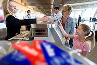 Mother and daughter 7-9 receiving ticket from female flight check-in attendant at airport check-in counter, smiling, side view
