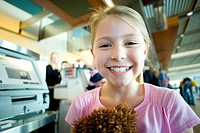 Blonde girl 7-9 standing near airport check-in counter, holding soft toy, smiling, close-up, portrait, focus on foreground