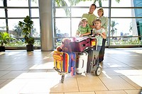 Family standing with luggage trolley in airport, smiling