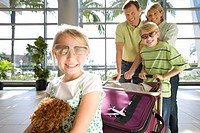 Family standing with luggage trolley in airport, girl 7-9 sitting on suitcase with soft toy in foreground, wearing sunglasses, smiling, portrait