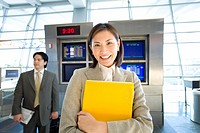 Businessman standing near flight information screen in airport, focus on businesswoman holding yellow folder in foreground, smiling, front view, portr...
