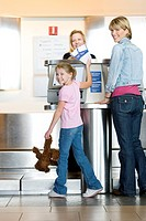 Mother and daughter 7-9 checking in at airport check-in desk, female check-in attendant passing boarding passes to girl, smiling, rear view, portrait