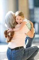 Grandmother and granddaughter 7-9 embracing in airport, senior woman crouching, girl holding soft toy, smiling