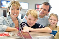 Family checking in at airport, boy 8-10 handing over passports, smiling, view from behind check-in desk