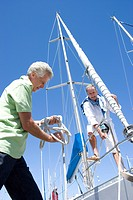 Two mature men preparing to set sail on yacht, one man untying mooring rope, smiling, low angle view