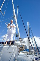 Mature man standing on deck of yacht in harbour, holding mooring rope, smiling, portrait