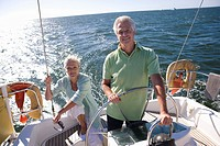 Mature couple sailing out at sea, man standing at helm of yacht, steering, woman sitting at stern, smiling, front view, portrait backlit