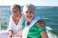 Mature couple sitting on deck of yacht out at sea, man with arm around woman, smiling, close-up, portrait