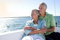 Mature couple sitting on deck of yacht out at sea, woman leaning contentedly against man, looking at view backlit