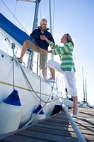 Chivalrous mature man assisting mature woman to board yacht moored at harbour jetty, offering helping hand, smiling, side view