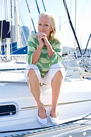 Mature woman, in green striped jumper, sitting on deck of yacht moored at harbour jetty, hands clasped together against chin, smiling, front view, por...