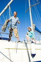 Mature couple setting sail on yacht, woman crouching on deck, man holding mooring rope, smiling, low angle view