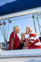 Mature couple, in red jumper and t-shirt, sitting on deck of yacht moored at harbour jetty, drinking white wine, smiling, side view